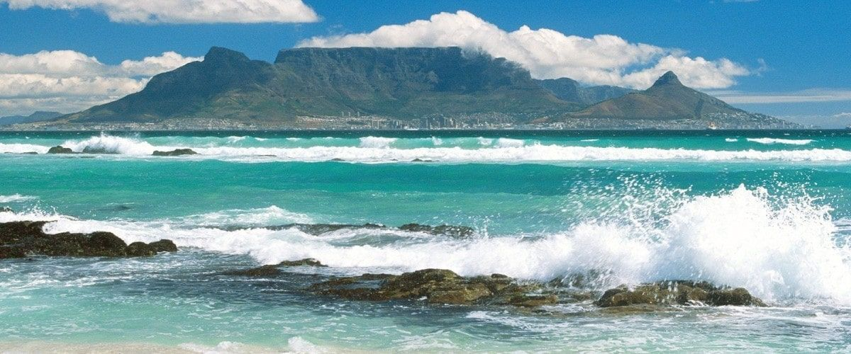 Table Mountain Cape Town seen across a turquoise ocean with crashing surf