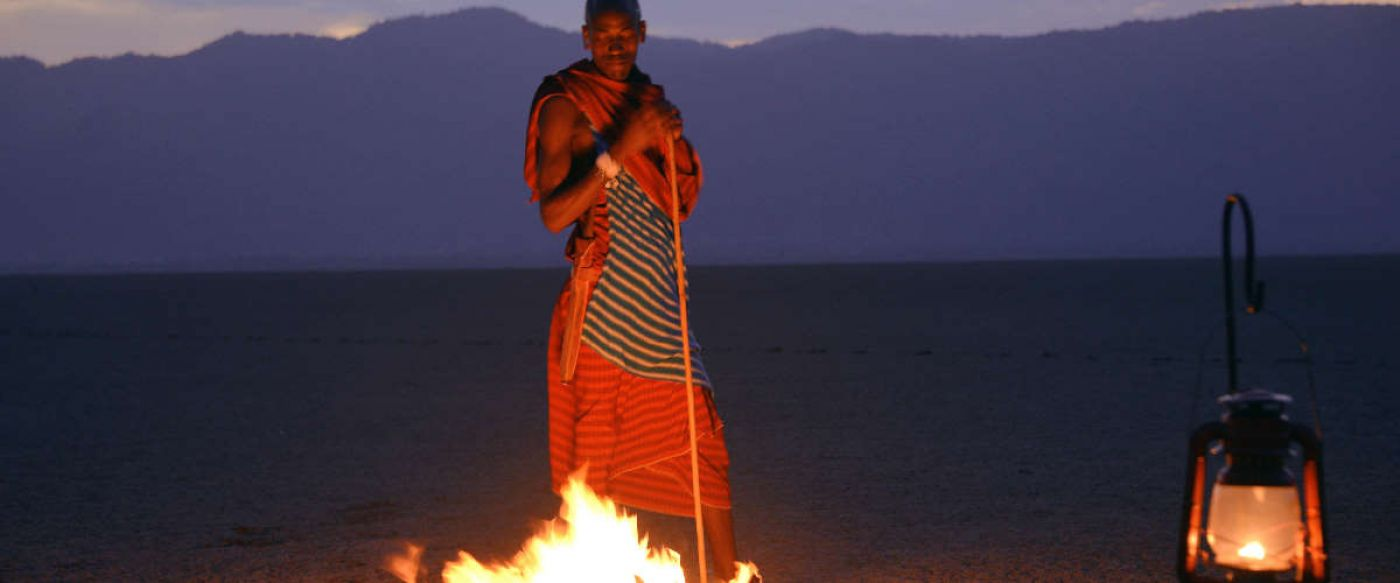 masai warrior standing next to camp fire in Tanzania