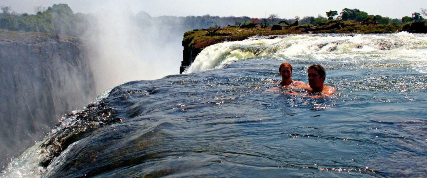 adventurous couple swimming in Devils Pool on the very edge of Victoria Falls